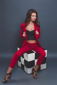 Modelo de moda en traje rojo. mujer joven posando con traje rojo sobre gris