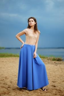 Modelo de moda tranquila y solitaria caminando sobre la arena en un día nublado en falda larga azul y blusa de encaje.