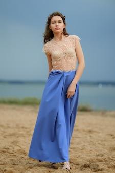 Modelo de moda tranquila y solitaria en la playa con falda azul y blusa transparente.
