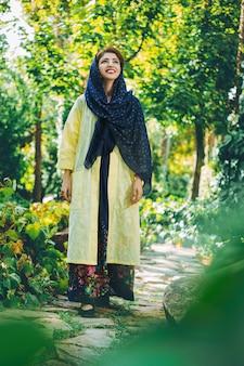 Modelo de moda en vestido beige con chal en la naturaleza