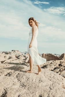 Modelo de moda en vestido blanco caminando sobre las piedras del desierto