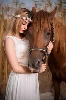 Modelo de moda en vestido blanco posando con un caballo