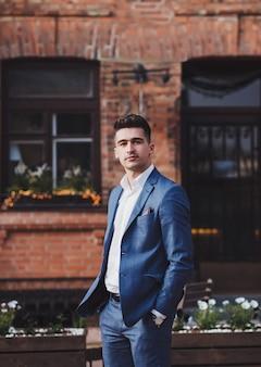 Modelo morena joven guapo, vestido con traje, mirando a cámara, posando en la ciudad. retrato de hombre de negocios.