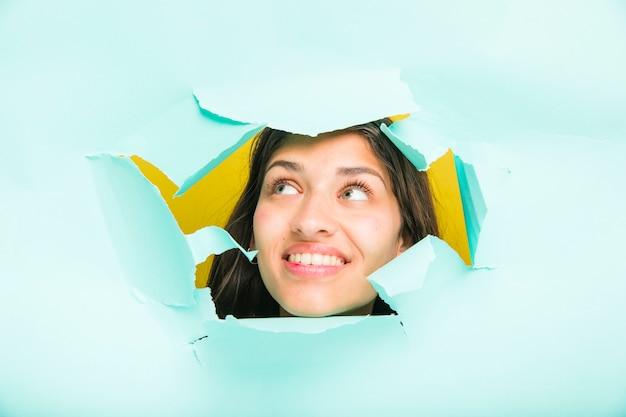 Modelo morena posando a través de agujero de papel
