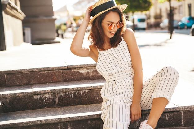 Modelo morena en ropa de verano posando en la calle posando