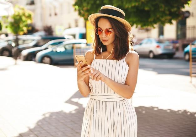 Modelo morena en ropa de verano posando en la calle mediante teléfono móvil