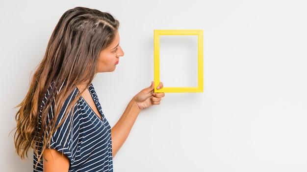Modelo morena sosteniendo marco amarillo