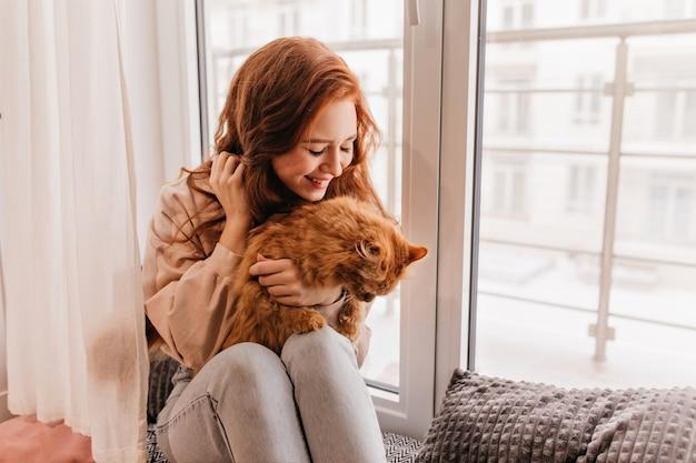 Modelo de mujer agradable con gato rojo de rodillas. retrato de interior de encantadora mujer jengibre posando con mascota.