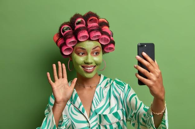 Modelo de mujer alegre con máscara facial verde, saluda con la palma y saluda a un amigo, tiene videoconferencia a través de un teléfono inteligente moderno, usa rulos para hacer un corte de cabello perfecto, vestido con ropa informal