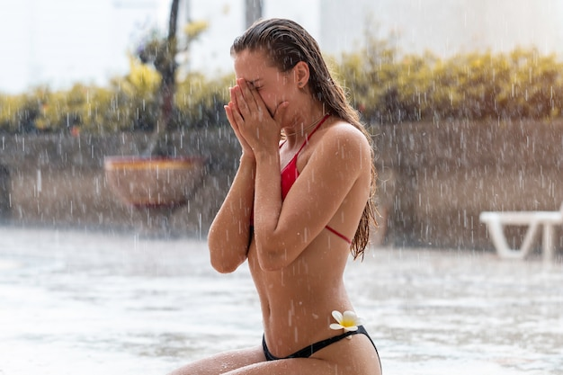 Modelo de mujer atractiva caucásica joven usar bikini bajo la lluvia.