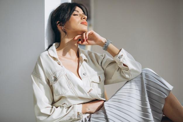 Modelo de mujer atractiva joven sentada junto a la pared