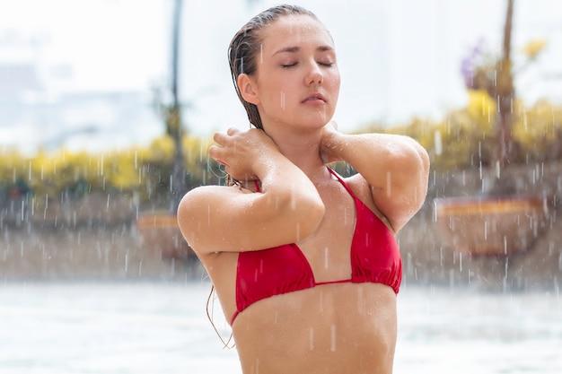 Modelo de mujer bastante caucásica usar bikini bajo la lluvia.