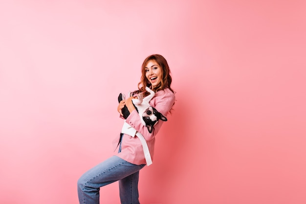 Modelo de mujer caucásica de buen humor en jeans posando con perro. alegre dama de jengibre sosteniendo bulldog francés y sonriendo.
