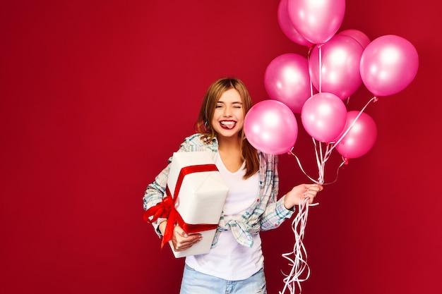 Modelo de mujer celebrando y sosteniendo caja con regalo presente y globos rosados