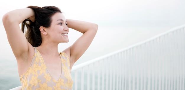 Modelo de mujer joven asiática sosteniendo su cabello