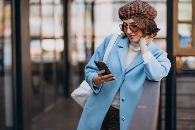 Modelo de mujer joven en bata azul junto al café, usando el teléfono