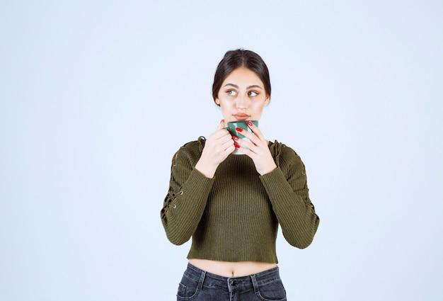 Un modelo de mujer joven y bonita bebiendo de una taza y mirando a otro lado.