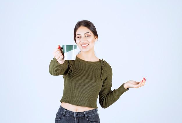 Un modelo de mujer joven y bonita que ofrece una taza de bebida caliente y mirando a la cámara.