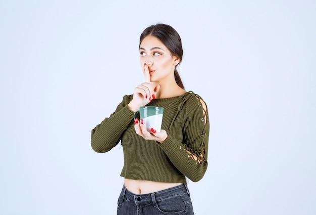 Un modelo de mujer joven y bonita sosteniendo una taza de bebida caliente y haciendo el signo de silencio.