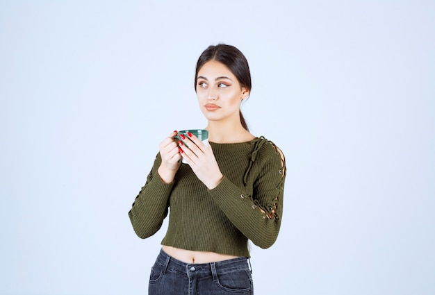 Un modelo de mujer joven y bonita sosteniendo una taza de bebida y mirando a otro lado.