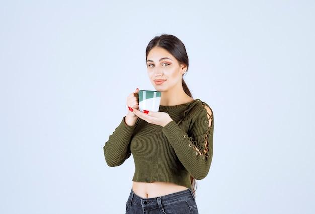 Un modelo de mujer joven y bonita sosteniendo una taza de bebida y de pie.