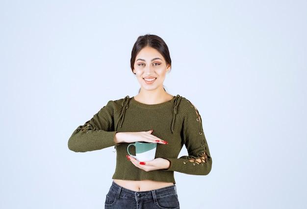 Un modelo de mujer joven y bonita sosteniendo una taza y mirando a la cámara