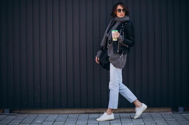 Modelo de mujer joven en chaqueta de cuero fuera de la calle