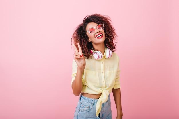 Modelo de mujer joven complacida en camisa de verano riendo. sincera niña africana con cabello rizado relajante