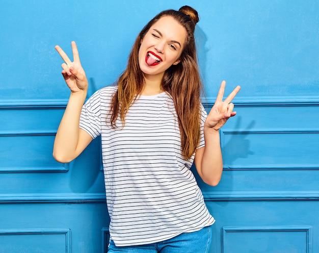 Modelo de mujer joven y elegante en ropa casual de verano con labios rojos, posando junto a la pared azul. guiñando un ojo y mostrando el signo de la paz