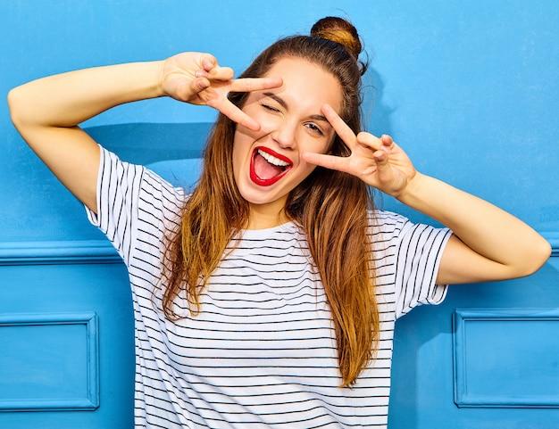 Modelo de mujer joven y elegante en ropa casual de verano con labios rojos, posando junto a la pared azul. parpadeo