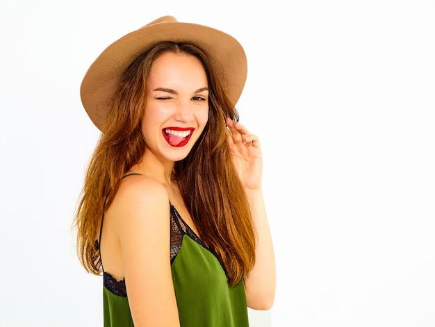Modelo de mujer joven y elegante en ropa casual de verano verde y sombrero marrón con labios rojos. guiñando un ojo y mostrando su lengua