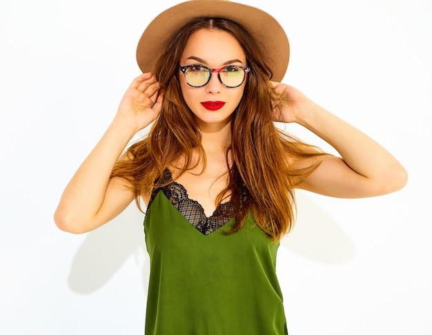 Modelo de mujer joven y elegante en ropa casual de verano verde y sombrero marrón con labios rojos, posando junto a la pared blanca