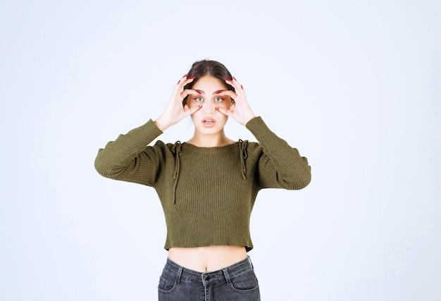 Un modelo de mujer joven y encantadora con ojos binoculares de pie sobre fondo blanco.