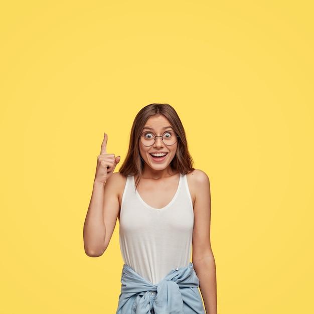 Modelo de mujer joven feliz feliz saliente se siente impresionada por algo hacia arriba, indica con el dedo índice