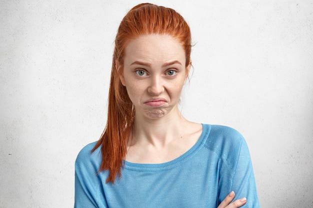 Modelo de mujer joven hermosa de pelo rojo disgustado con algo, labios curvas y tiene expresión de descontento, expresa negatividad