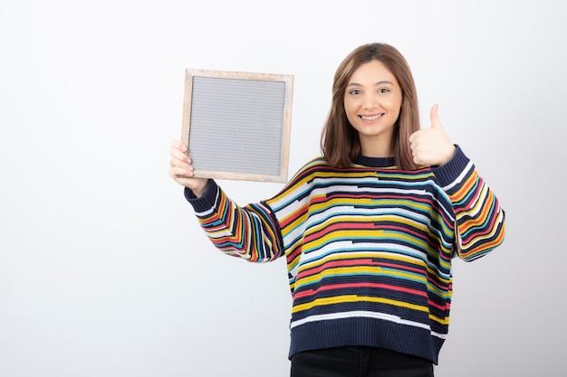 Modelo de mujer joven con un marco que muestra un pulgar hacia arriba.