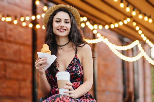Modelo de mujer joven con ojos oscuros, labios pintados de rojo con vestido de verano y sombrero sosteniendo en las manos café para llevar