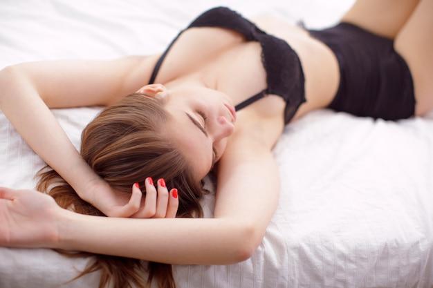 Modelo de mujer joven sexy acostada en la cama
