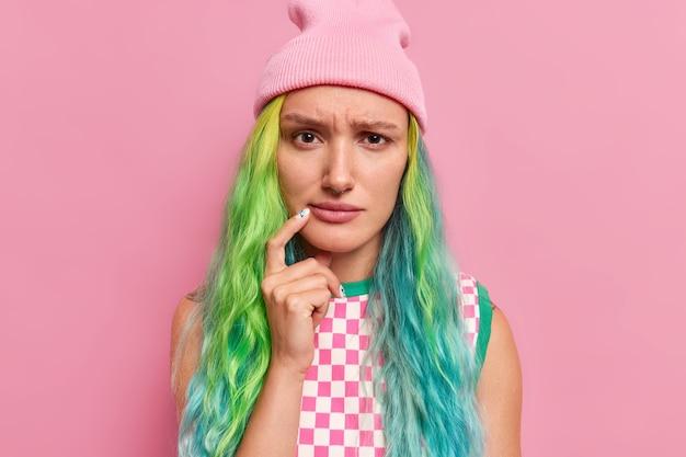 Modelo de mujer joven triste con el pelo largo teñido mantiene el dedo cerca de la esquina de los labios parece disgustado tiene expresión enfurruñada usa sombrero vestido a cuadros aislado en rosa