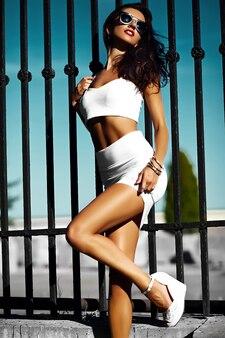 Modelo de mujer de moda en tela blanca con gafas de sol en la calle detrás del cielo azul
