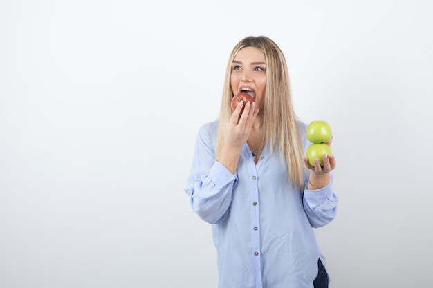 Modelo de mujer muy atractiva de pie y comiendo una manzana roja fresca.