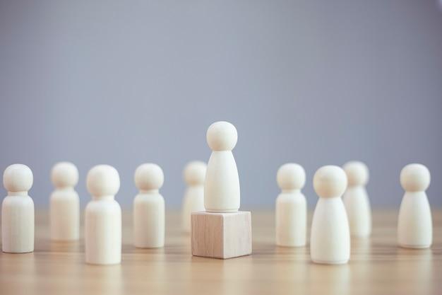 Modelo de mujer de persona de madera entre personas sobre fondo negro concepto de liderazgo