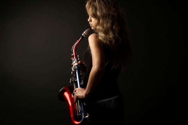 Modelo de mujer rubia atractiva sexy con saxofón