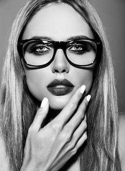 Modelo de mujer rubia hermosa caliente con maquillaje diario fresco con color de labios oscuros y piel limpia y sana sobre fondo rojo en gafas