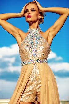 Modelo de mujer rubia sexy joven en vestido amarillo de noche posando sobre fondo de cielo azul
