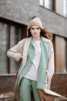 Modelo de mujer con sombrero y abrigo en la escena del paisaje urbano posando