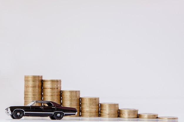 Un modelo negro de un automóvil con monedas en forma de histograma sobre un fondo blanco. concepto de préstamos, ahorros, seguros.
