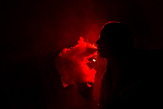 Modelo de niña fuma vape en luz roja. de cerca.