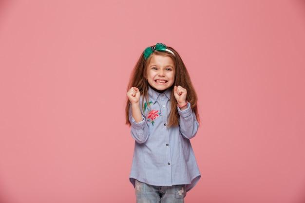 Modelo de niña sonriente en aro de pelo y ropa de moda que expresa felicidad gesticulando con los puños cerrados