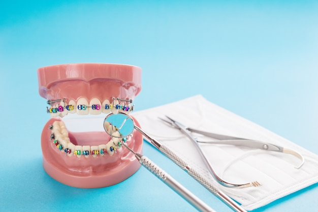Modelo ortodóntico y herramienta de dentista sobre fondo azul